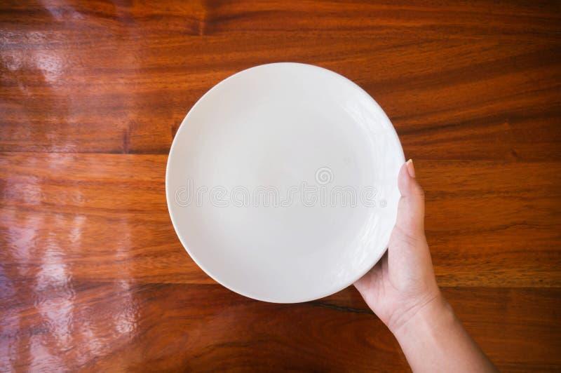 Θηλυκό & x28 woman& x29  λαβή & x28 χεριών support& x29  ένα άσπρα πιάτο & x28 plate& x29  στο ξύλο στοκ εικόνα