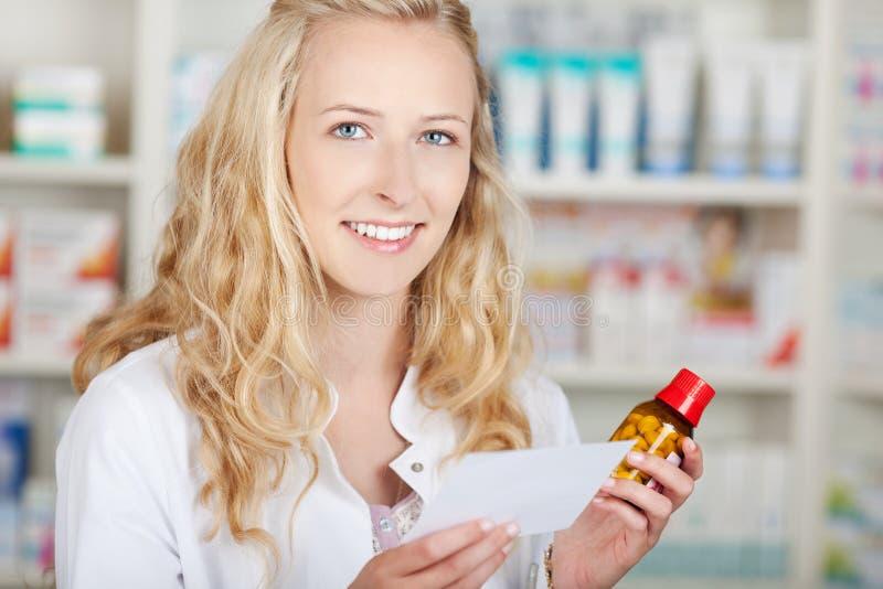 Θηλυκά έγγραφο και μπουκάλι συνταγών εκμετάλλευσης φαρμακοποιών στοκ εικόνες