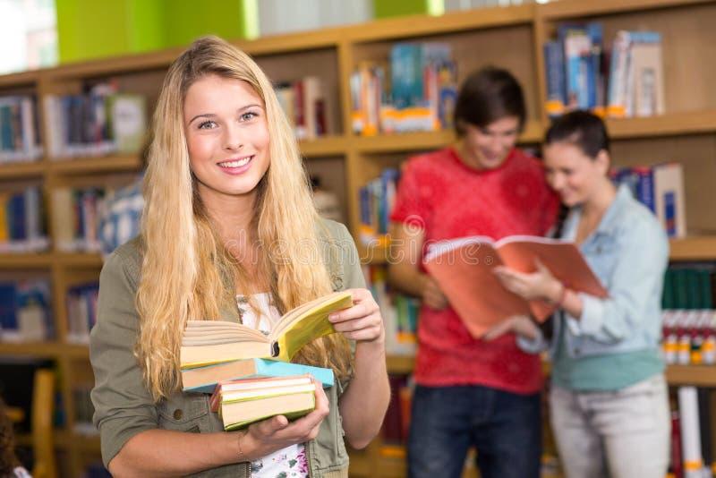 Θηλυκά βιβλία εκμετάλλευσης φοιτητών πανεπιστημίου στη βιβλιοθήκη στοκ εικόνα με δικαίωμα ελεύθερης χρήσης