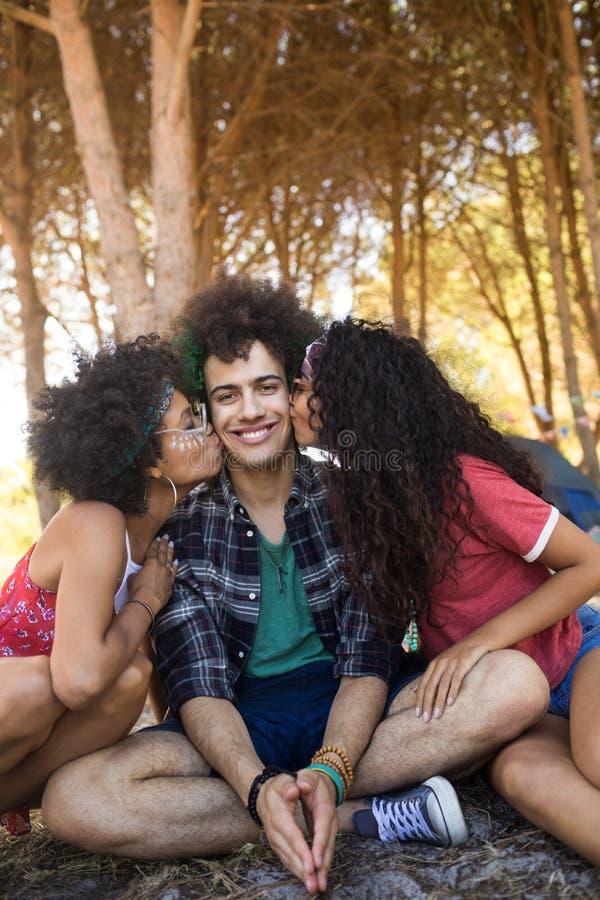 Θηλυκά που φιλούν τους νέους αρσενικούς φίλους που κάθονται στον τομέα στοκ εικόνες