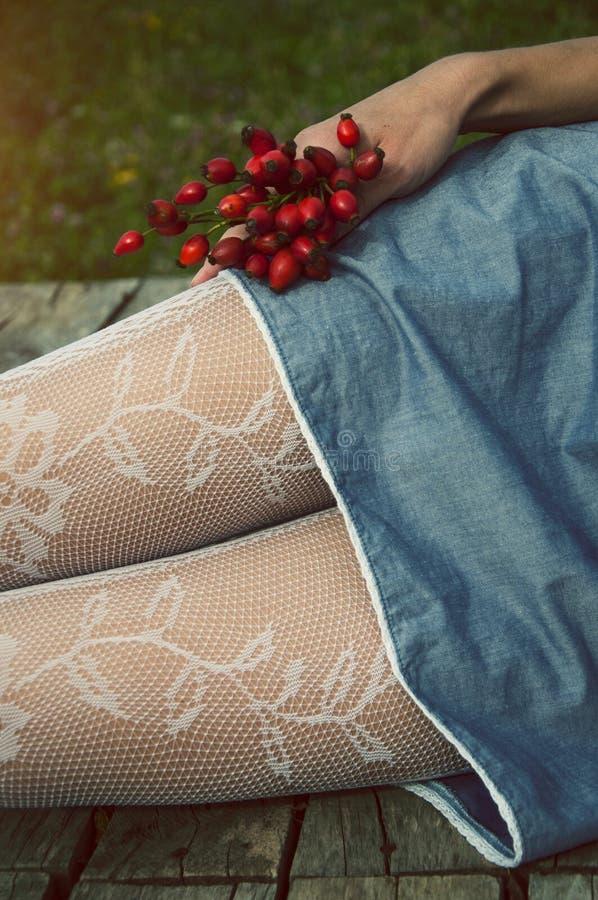Θηλυκά πόδια και ένας κάδος των ροδαλών ισχίων στοκ φωτογραφία