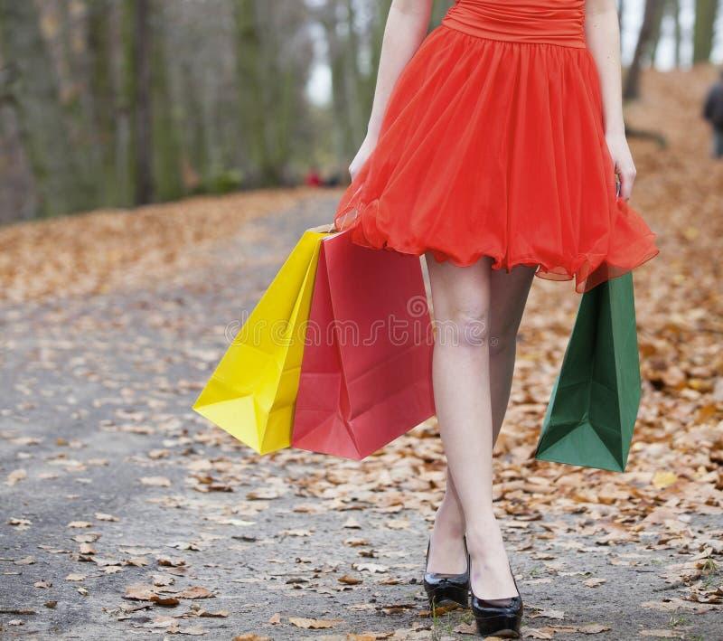 Θηλυκά πόδια και ψωνίζοντας γυναίκα τσαντών στο φθινοπωρινό πάρκο στοκ εικόνα