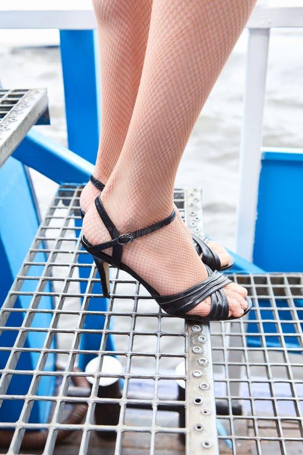 Θηλυκά πόδια ομορφιάς στα καλσόν διχτυών ψαρέματος και παπούτσια στα υψηλά τακούνια στα σκαλοπάτια στοκ εικόνες