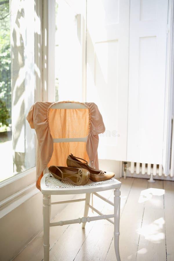 Θηλυκά σακάκι και παπούτσια στην έδρα στοκ φωτογραφία