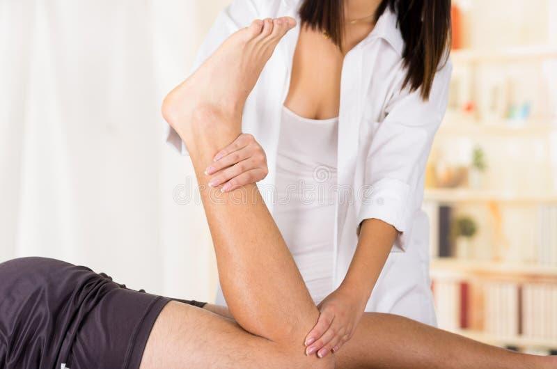 Θηλυκά φυσιο χέρια θεραπόντων που λειτουργούν στα αρσενικά πόδια ασθενών, εκμετάλλευση και κάμψη, μουτζουρωμένο υπόβαθρο κλινικών στοκ φωτογραφίες με δικαίωμα ελεύθερης χρήσης