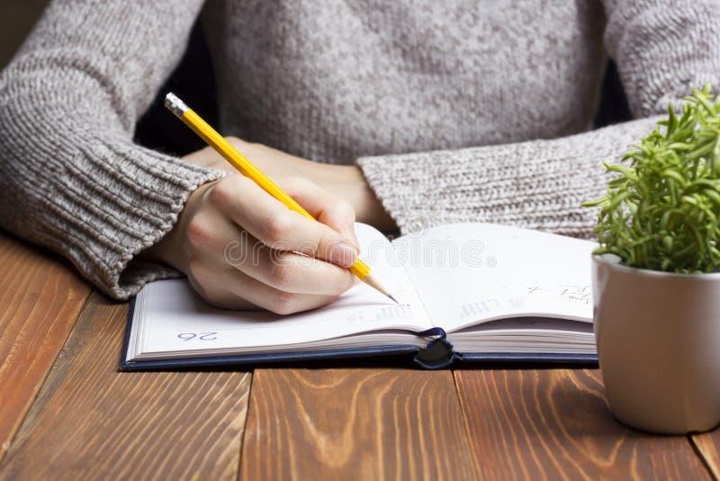 Θηλυκά χέρια με το μολύβι που γράφει στο σημειωματάριο στοκ εικόνες με δικαίωμα ελεύθερης χρήσης