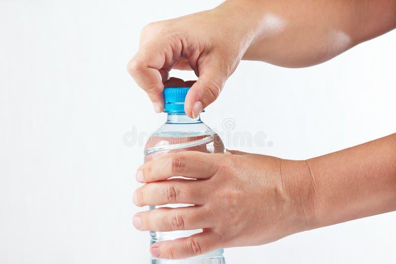 Θηλυκά χέρια που ανοίγουν το μπουκάλι νερό στοκ φωτογραφίες