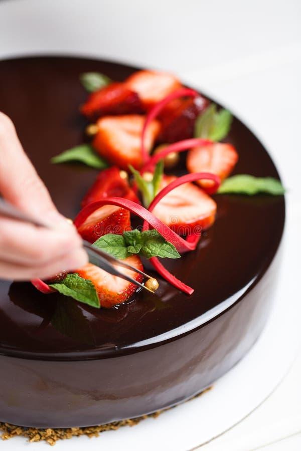 Θηλυκά χέρια που διακοσμούν το κέικ στοκ φωτογραφίες με δικαίωμα ελεύθερης χρήσης
