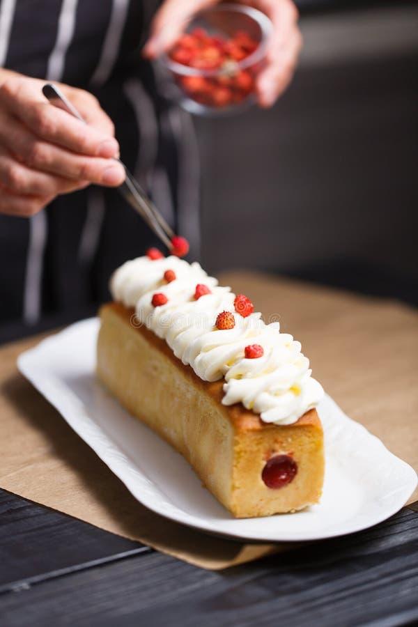 Θηλυκά χέρια που διακοσμούν το κέικ στοκ εικόνες με δικαίωμα ελεύθερης χρήσης