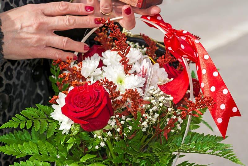 Θηλυκά χέρια που κρατούν ένα καλάθι των λουλουδιών στοκ φωτογραφία με δικαίωμα ελεύθερης χρήσης