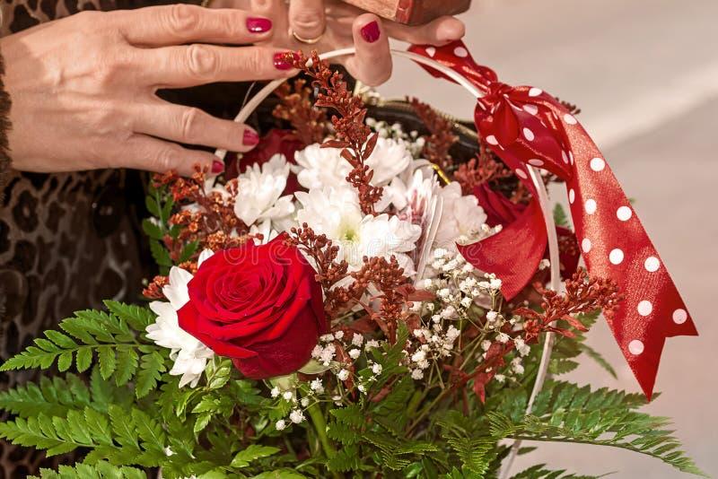 Θηλυκά χέρια που κρατούν ένα καλάθι των λουλουδιών στοκ φωτογραφία