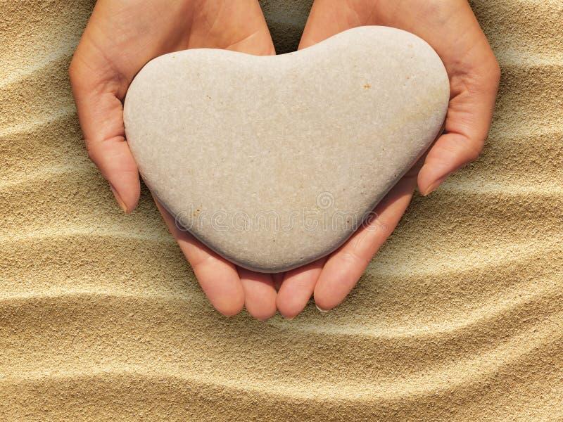 Θηλυκά χέρια που κρατούν μια καρδιά-διαμορφωμένη πέτρα στοκ εικόνες