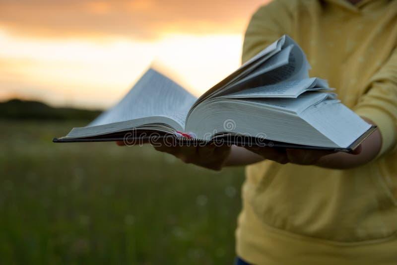 Θηλυκά χέρια που κρατούν το ανοιγμένο βιβλίο βιβλίων με σκληρό εξώφυλλο, ημερολόγιο με αερισμένος pag στοκ φωτογραφία με δικαίωμα ελεύθερης χρήσης