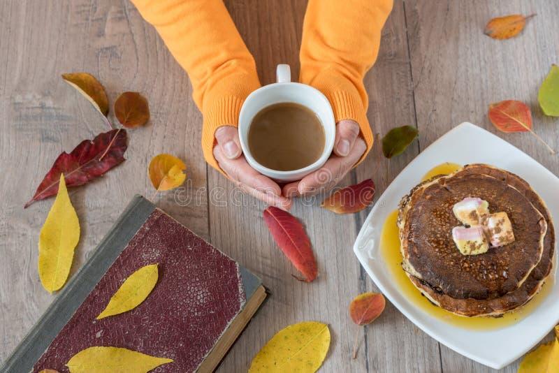 Θηλυκά χέρια που κρατούν το φλιτζάνι του καφέ στο ξύλινο υπόβαθρο Φθινόπωρο στοκ φωτογραφίες