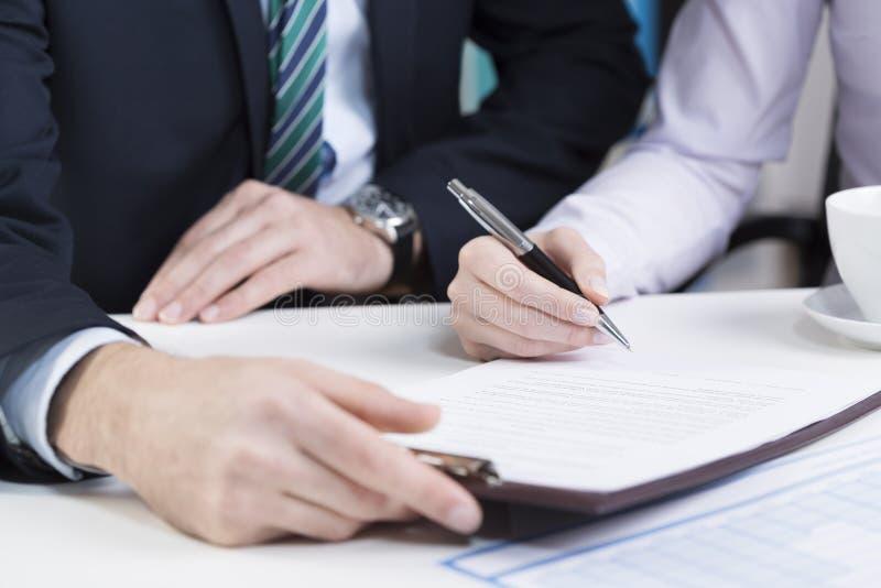 Θηλυκά χέρια που υπογράφουν τη σύμβαση στοκ εικόνες με δικαίωμα ελεύθερης χρήσης