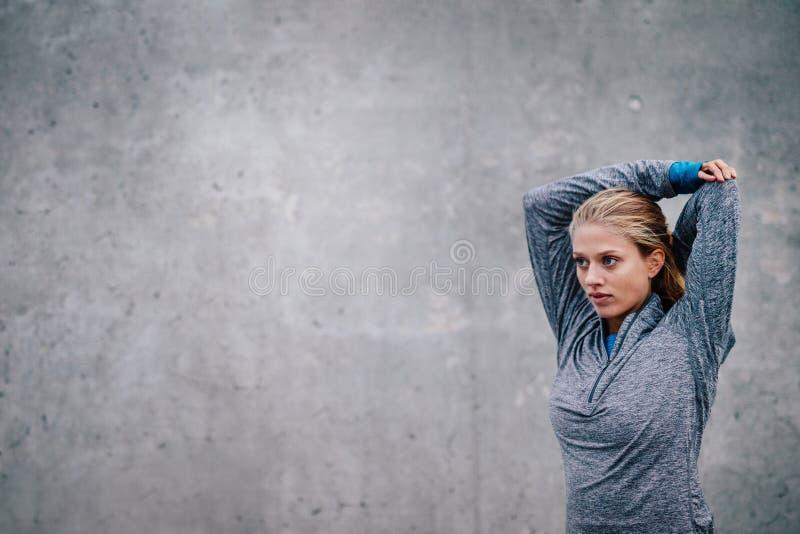 Θηλυκά όπλα τεντώματος δρομέων μετά από μια τρέχοντας σύνοδο στοκ φωτογραφίες