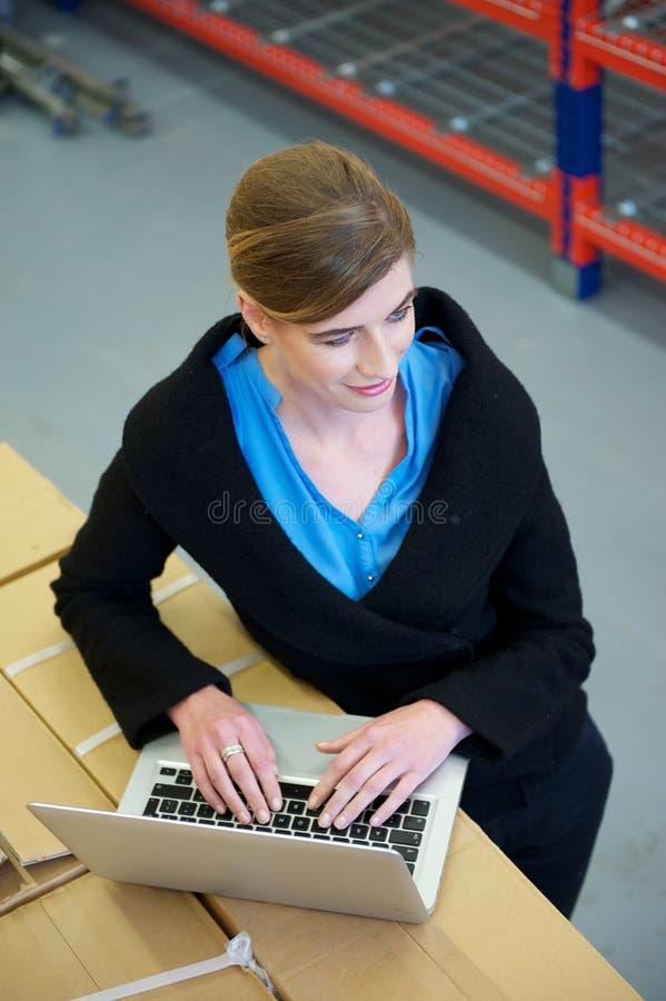 Θηλυκή δακτυλογράφηση εργαζομένων στο φορητό προσωπικό υπολογιστή στην αποθήκη εμπορευμάτων στοκ φωτογραφίες
