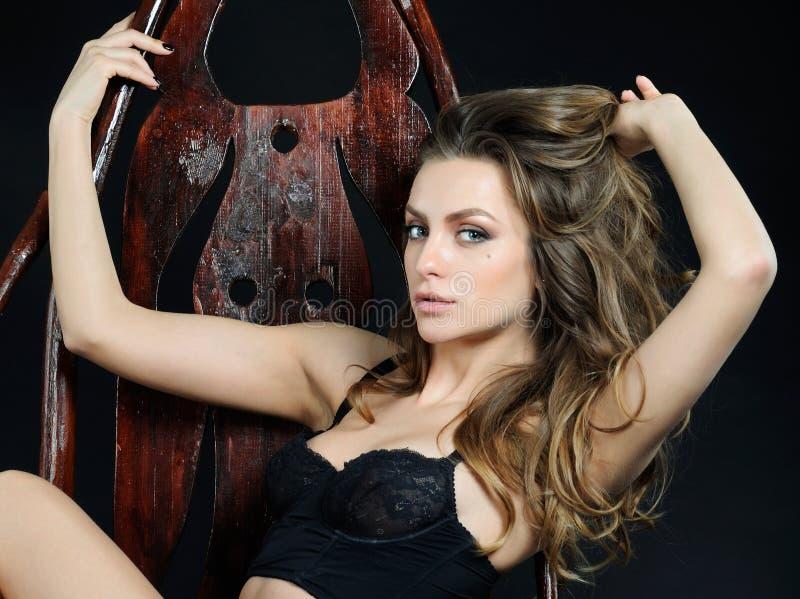 Θηλυκή ευαίσθητη συναισθηματική γυναίκα στο εσώρουχο δαντελλών στο ξύλινο cha στοκ φωτογραφία με δικαίωμα ελεύθερης χρήσης