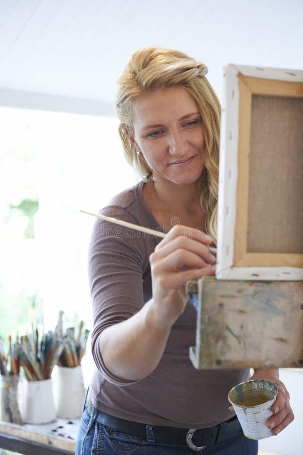 Θηλυκή ζωγραφική καλλιτεχνών στο στούντιο στοκ εικόνες με δικαίωμα ελεύθερης χρήσης
