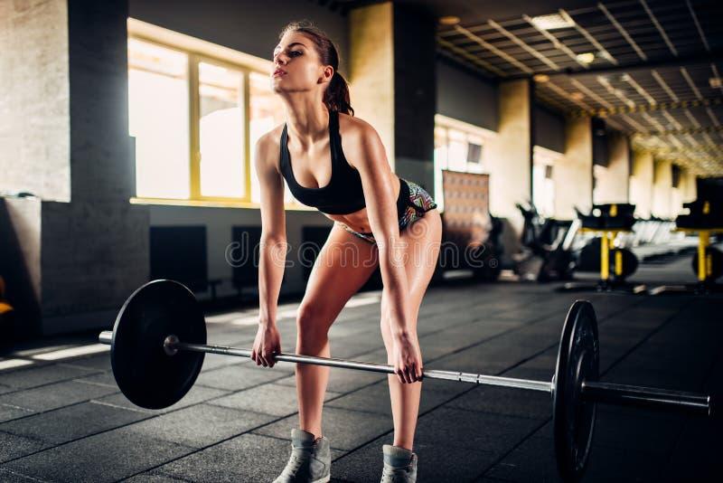 Θηλυκή κατάρτιση αθλητών με το barbell στην αθλητική γυμναστική στοκ εικόνα