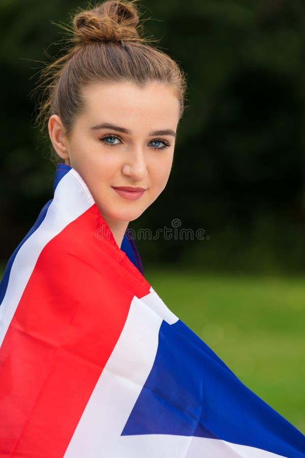 Θηλυκή νέα γυναίκα έφηβη που τυλίγεται στη σημαία του Union Jack στοκ εικόνα