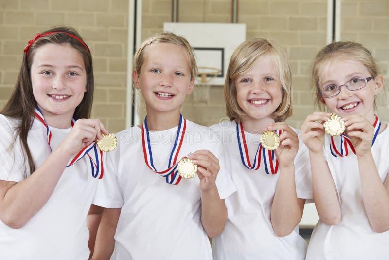 Θηλυκή ομάδα σχολικού αθλητισμού στη γυμναστική με τα μετάλλια στοκ φωτογραφία