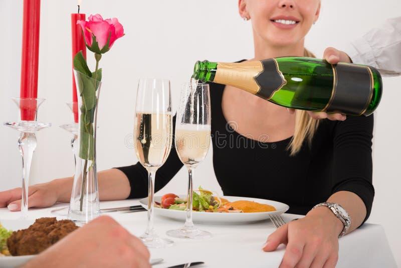 Θηλυκή σερβιτόρα που χύνει CHAMPAGNE στο γυαλί για το ζεύγος στοκ φωτογραφία με δικαίωμα ελεύθερης χρήσης