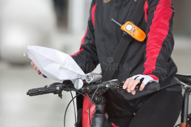 Θηλυκή συσκευασία αγγελιαφόρων εκμετάλλευσης ποδηλατών στοκ εικόνα