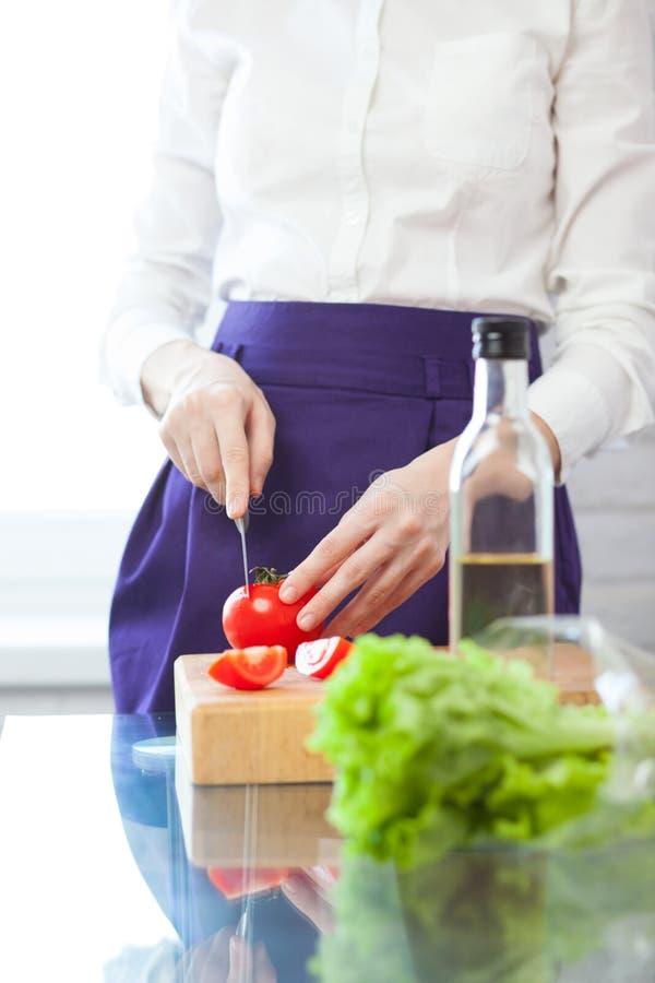 Θηλυκή τέμνουσα ντομάτα αρχιμαγείρων στοκ εικόνες