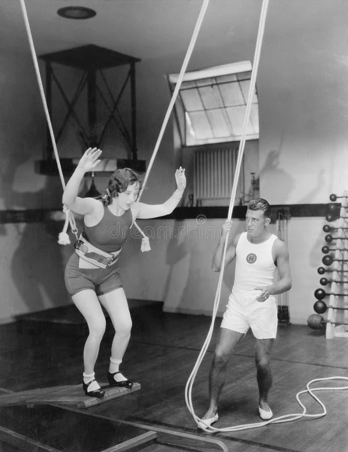 Θηλυκή gymnast κατάρτιση με τα σχοινιά ασφάλειας με το λεωφορείο (όλα τα πρόσωπα που απεικονίζονται δεν ζουν περισσότερο και κανέ στοκ φωτογραφίες