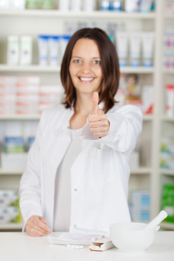 Θηλυκοί αντίχειρες Gesturing φαρμακοποιών επάνω στο μετρητή φαρμακείων στοκ φωτογραφίες