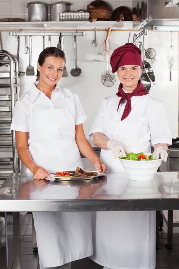 Θηλυκοί αρχιμάγειρες με τα πιάτα στο μετρητή κουζινών στοκ φωτογραφία