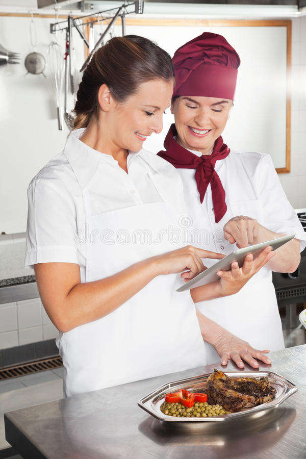 Θηλυκοί αρχιμάγειρες που χρησιμοποιούν την ψηφιακή ταμπλέτα στην κουζίνα στοκ φωτογραφία με δικαίωμα ελεύθερης χρήσης