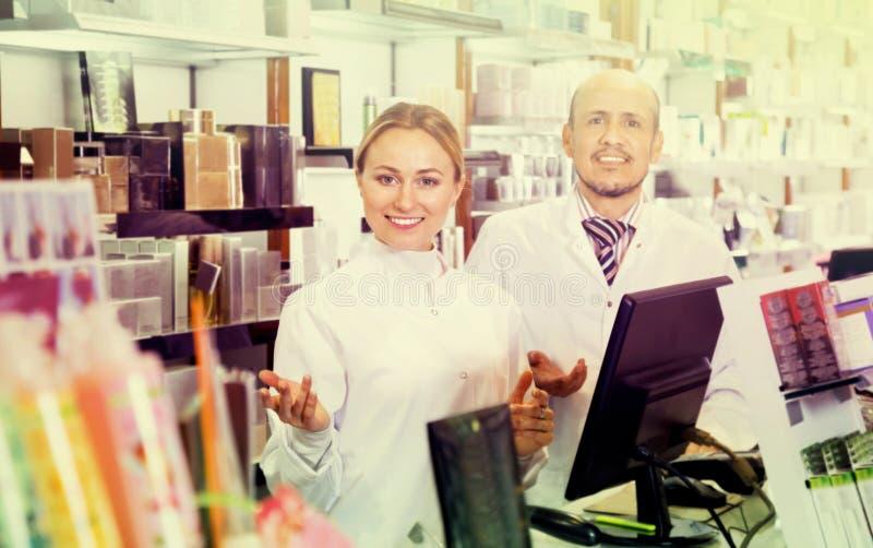Θηλυκοί και αρσενικοί φαρμακοποιοί που απασχολούνται στο φαρμακευτικό κατάστημα στοκ φωτογραφία με δικαίωμα ελεύθερης χρήσης