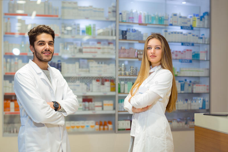 Θηλυκοί και αρσενικοί φαρμακοποιοί στο φαρμακείο στοκ εικόνες