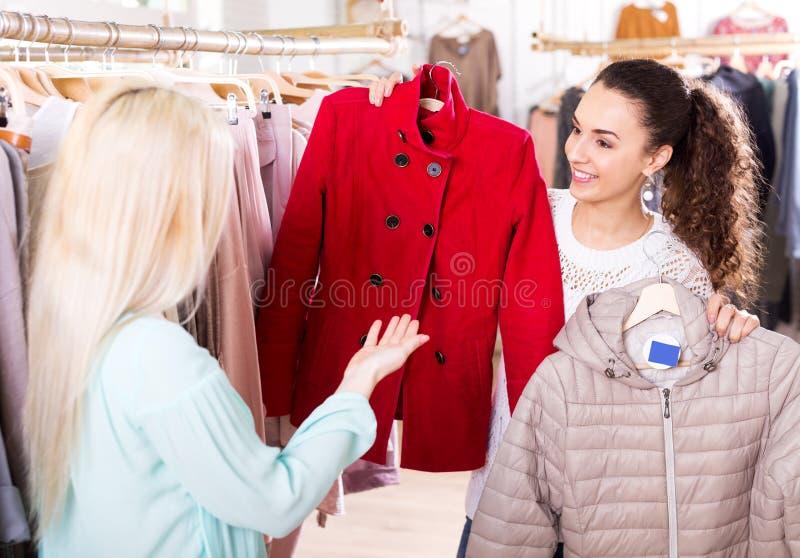 Θηλυκοί πελάτες που επιλέγουν τα παλτά και τα σακάκια στοκ εικόνες