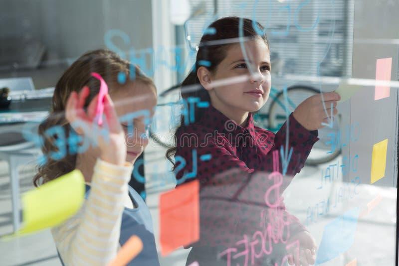 Θηλυκοί συνάδελφοι που τα στοιχεία που βλέπουν μέσω του γυαλιού στοκ φωτογραφία