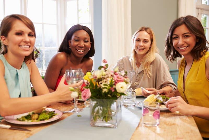 Θηλυκοί φίλοι που κάθονται στο σπίτι τον πίνακα για το κόμμα γευμάτων στοκ εικόνες με δικαίωμα ελεύθερης χρήσης
