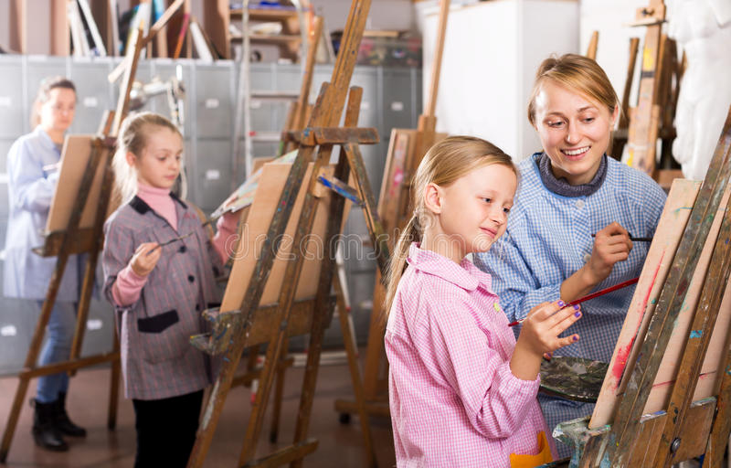 Θηλυκός δάσκαλος που βοηθά το κορίτσι κατά τη διάρκεια της κατηγορίας ζωγραφικής στοκ φωτογραφίες με δικαίωμα ελεύθερης χρήσης