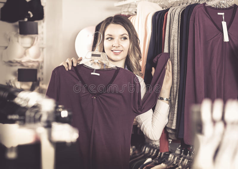 Θηλυκός αγοραστής που εξετάζει τα μακριά πουκάμισα μανικιών στο κατάστημα εσώρουχων στοκ φωτογραφία με δικαίωμα ελεύθερης χρήσης