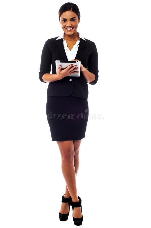 Θηλυκός ανώτερος υπάλληλος που χρησιμοποιεί το μαξιλάρι αφής, πλήρης πυροβολισμός μήκους στοκ εικόνες