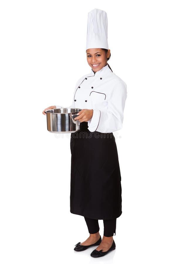 Θηλυκός αρχιμάγειρας με να μαγειρεψει το δοχείο υπό εξέταση στοκ εικόνα