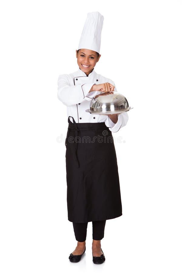 Θηλυκός αρχιμάγειρας με το δίσκο των τροφίμων στη διάθεση στοκ εικόνα
