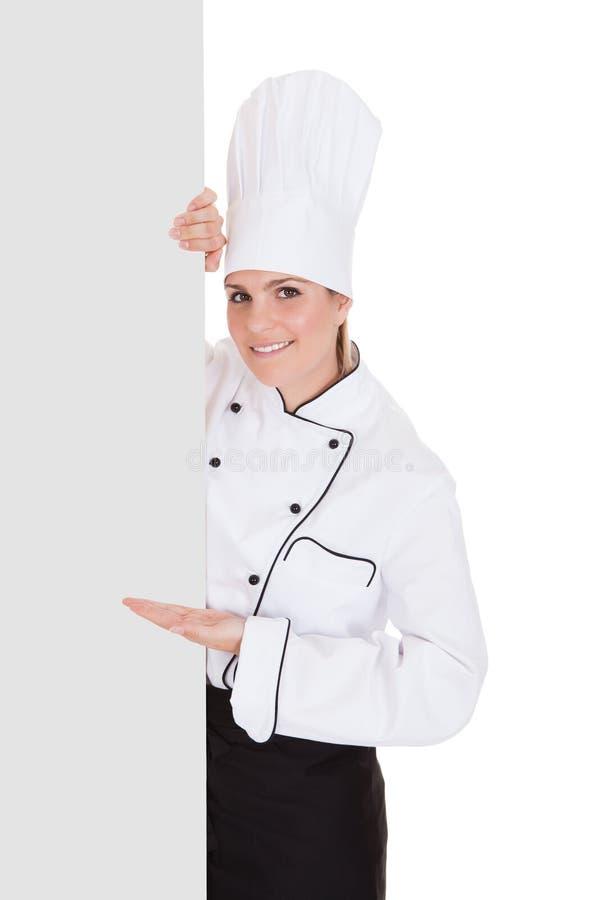 Θηλυκός αρχιμάγειρας που παρουσιάζει κενή αφίσσα στοκ εικόνες με δικαίωμα ελεύθερης χρήσης