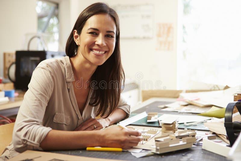 Θηλυκός αρχιτέκτονας που κάνει πρότυπο στην αρχή στοκ φωτογραφία