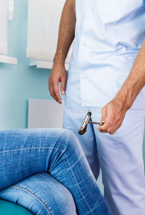 Θηλυκός ασθενής γονάτων σφυριών γιατρών prostukivet στο γραφείο του medetsinkom Ο γιατρός εξετάζει το patient& x27 γόνατο του s στοκ φωτογραφία