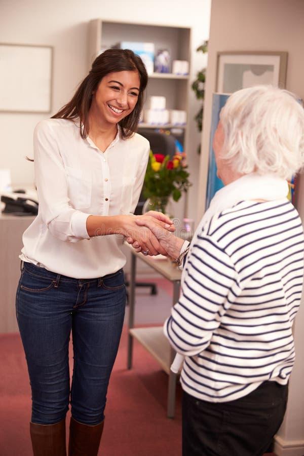 Θηλυκός ασθενής χαιρετισμού ρεσεψιονίστ στην κλινική ακρόασης στοκ φωτογραφία