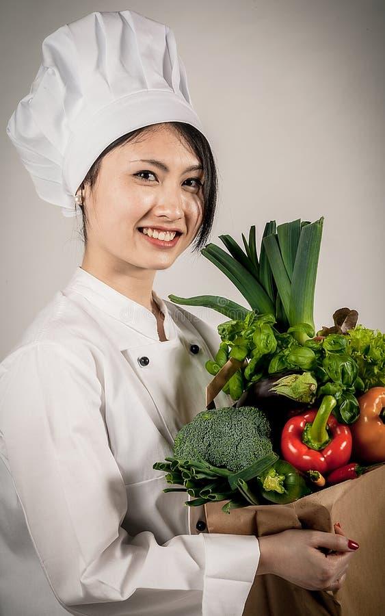 Θηλυκός ασιατικός αρχιμάγειρας με την τσάντα εγγράφου των λαχανικών στοκ εικόνες με δικαίωμα ελεύθερης χρήσης