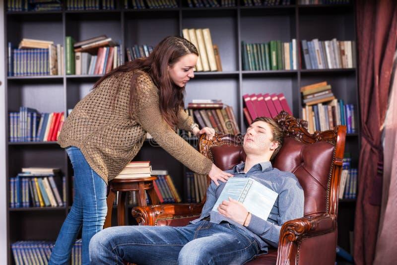 Θηλυκός βιβλιοθηκάριος που ξυπνά έναν νεαρό άνδρα ύπνου στοκ φωτογραφία με δικαίωμα ελεύθερης χρήσης
