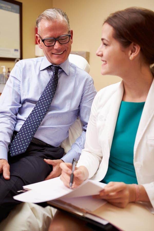 Θηλυκός γιατρός κατόπιν διαβουλεύσεων με τον αρσενικό ασθενή στοκ εικόνες